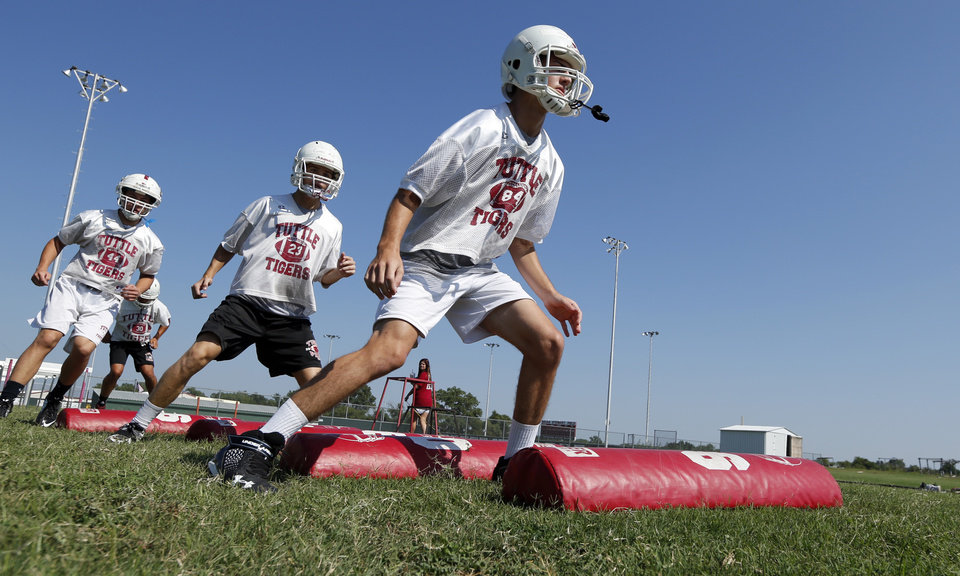 Photo - Trenton Slattery, Brady Combes and Joseph Stone go through stretching drills during high school football practice on Tuesday, Aug. 12, 2014 in Tuttle, Okla. Photo by Steve Sisney, The Oklahoman