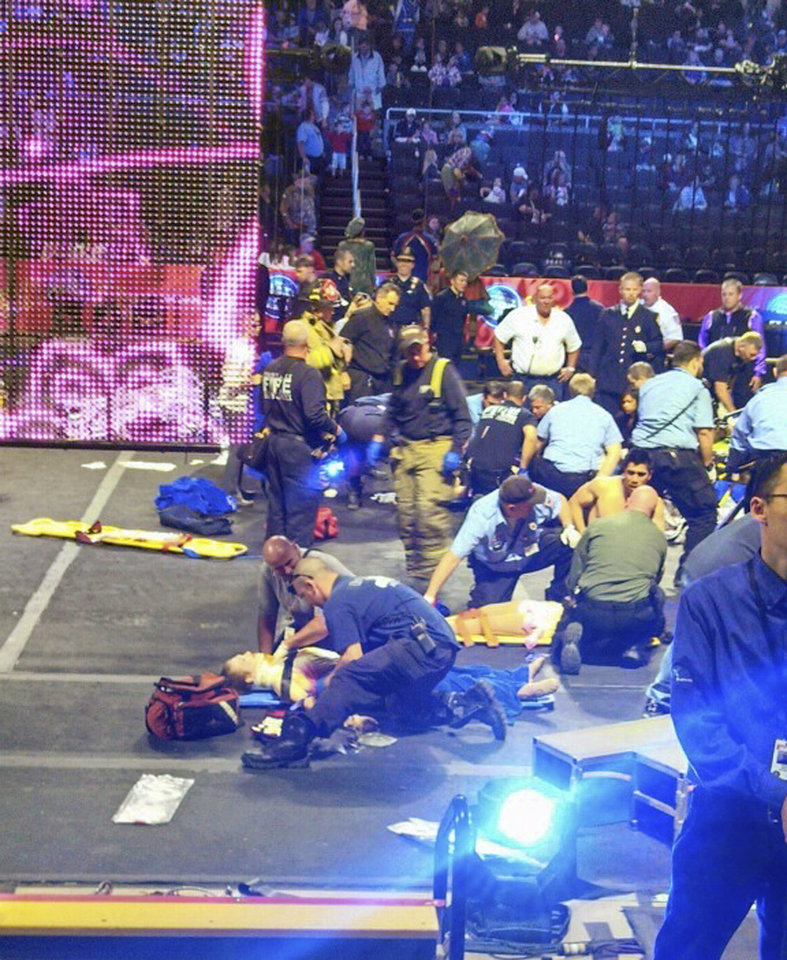 Photo - In this photo provided by Rose Viveiros, first responders work at the center ring after a platform collapsed during an aerial hair-hanging stunt at the Ringling Brothers and Barnum and Bailey Circus, Sunday, May 4, 2014, in Providence, R.I. At least nine performers were seriously injured in the fall, including a dancer below, while an unknown number of others suffered minor injuries. (AP Photo/Rose Viveiros) MANDATORY CREDIT