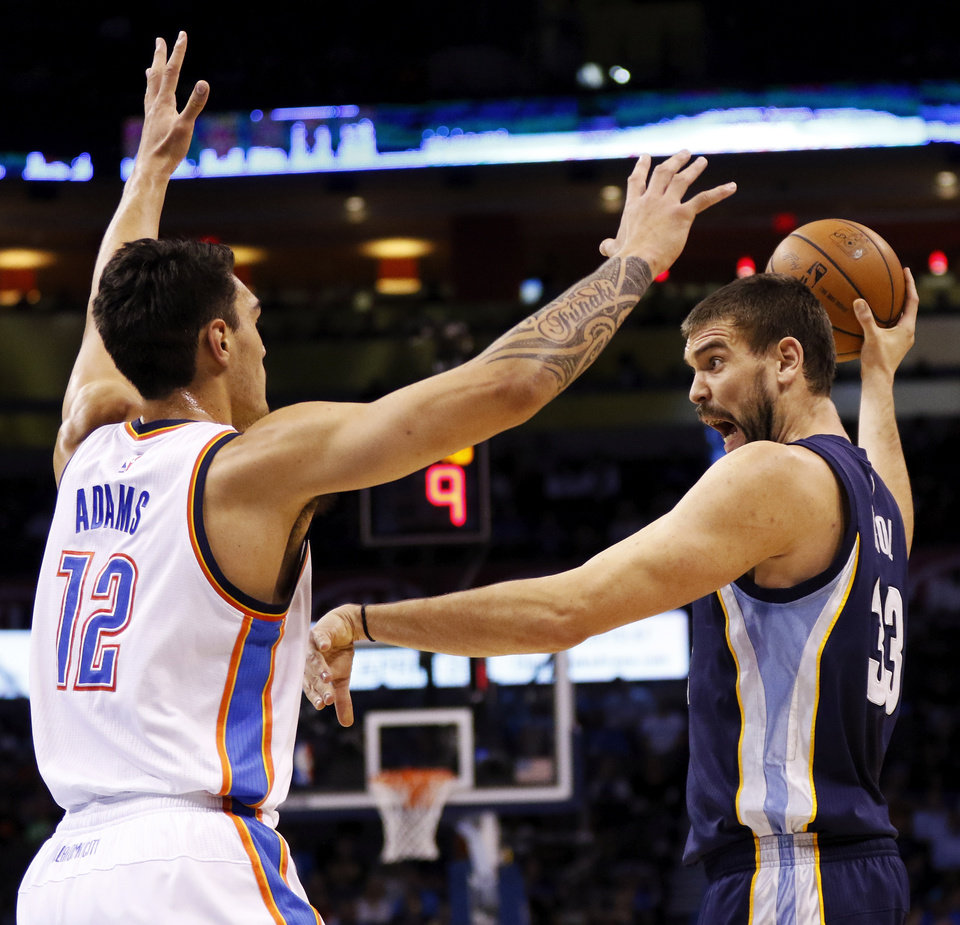 Photo - FILE - Memphis' Marc Gasol (33) passes away from Oklahoma City's Steven Adams (12) during an NBA basketball game between the Oklahoma City Thunder and the Memphis Grizzlies at Chesapeake Energy Arena in Oklahoma City, Friday, Nov. 7, 2014. Photo by Nate Billings, The Oklahoman