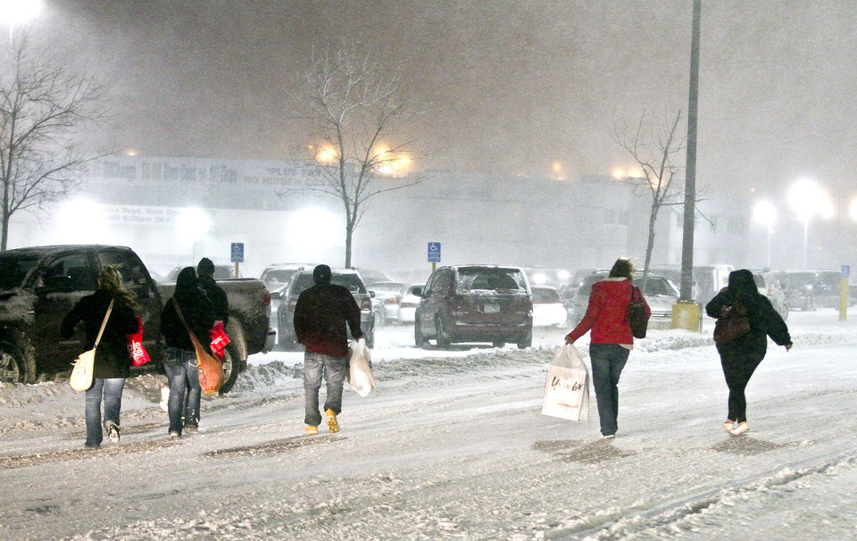 Photo -   Shoppers hurry to their vehicles after shopping during Black Friday sales at Miller Hill Mall in Duluth, Minn., Friday, Nov. 23, 2012. Black Friday, the day when retailers traditionally turn a profit for the year, got a jump start this year as many stores opened just as families were finishing up Thanksgiving dinner. (AP Photo/The Duluth News-Tribune, Clint Austin)