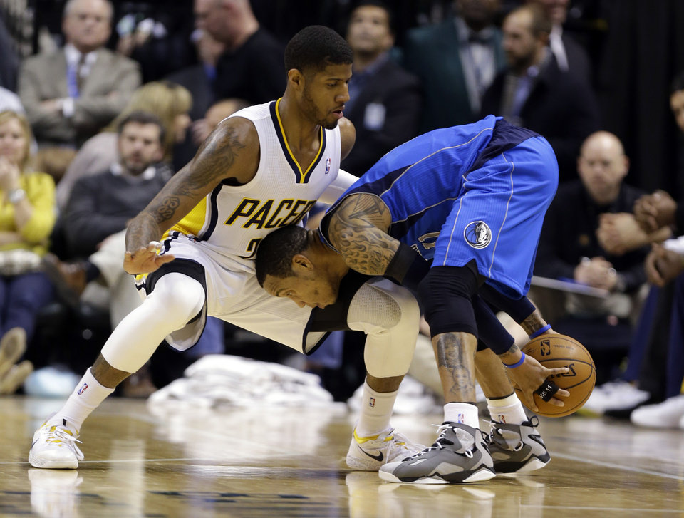 Photo - Indiana Pacers forward Paul George, left, defends Dallas Mavericks guard Monta Ellis during the second half of an NBA basketball game in Indianapolis, Wednesday, Feb. 12, 2014. The mavericks defeated the Pacers 81-73. (AP Photo/Michael Conroy)