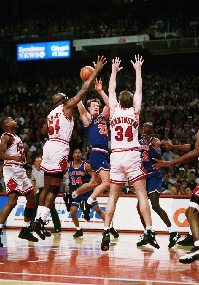 Photo - Chicago Bulls' Horace Grant (54) and Bill Wennington (34) double team Cleveland Cavaliers guard Mark Price during the first half of their first-round NBA playoff game in Chicago,- Sunday, May 1, 1994. (AP Photo/Barry Jarvinen)