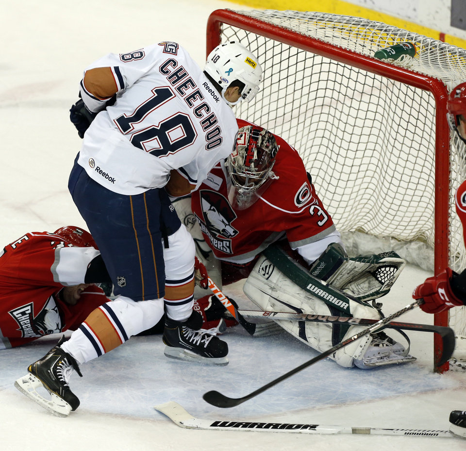 Baron's Jonathan Cheechoo scores between the legs of goalie Rob Madore in the first period during Game 2 of the AHL hockey playoff series between the Oklahoma City Barons and the Charlotte Checkers at the Cox Center in Oklahoma City, on Saturday, April 27, 2013.  Photo by Steve Sisney, The Oklahoman