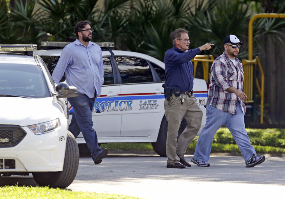 Photo - George Zimmerman, far right, is escorted to a home by a Lake Mary police officer, center, and Shawn Vincent, as assistant to his attorney, Monday, Sept. 9, 2013, in Lake Mary, Fla., after a domestic incident in the neighborhood where Zimmerman and his wife Shellie had lived during his murder trial. Zimmerman's wife says on a 911 call that her estranged husband punched her father in the nose, grabbed an iPad out of her hand and smashed it and threatened them both with a gun. Zimmerman was recently found not guilty for the 2012 shooting death of Trayvon Martin. (AP Photo/John Raoux)