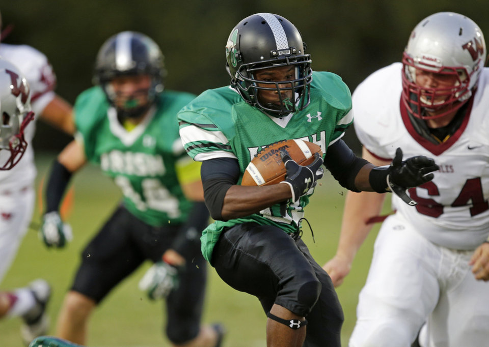 Photo - Billy Vivian of Bishop McGuinness runs past Weatheford's Kolton Kardokus during their high school football game in Oklahoma City, Friday, Sept. 20, 2013. Photo by Bryan Terry, The Oklahoman