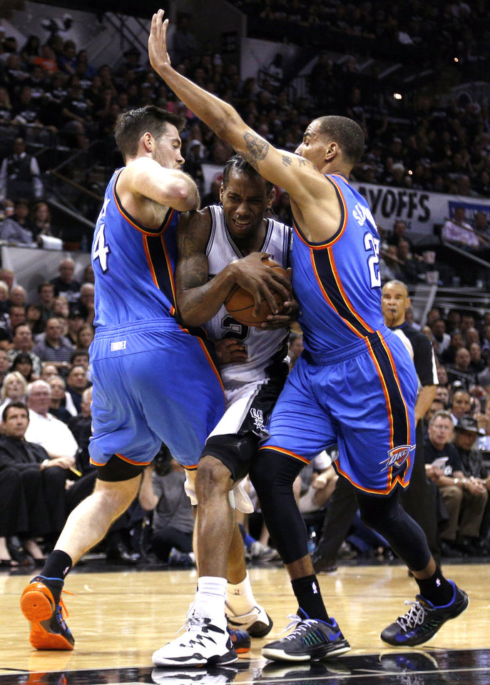 Photo - San Antonio's Kawhi Leonard (2) drives in between Oklahoma City's Nick Collison (4) and Oklahoma City's Thabo Sefolosha (25) during Game 1 of the Western Conference Finals in the NBA playoffs between the Oklahoma City Thunder and the San Antonio Spurs at the AT&T Center in San Antonio, Monday, May 19, 2014. Photo by Sarah Phipps, The Oklahoman