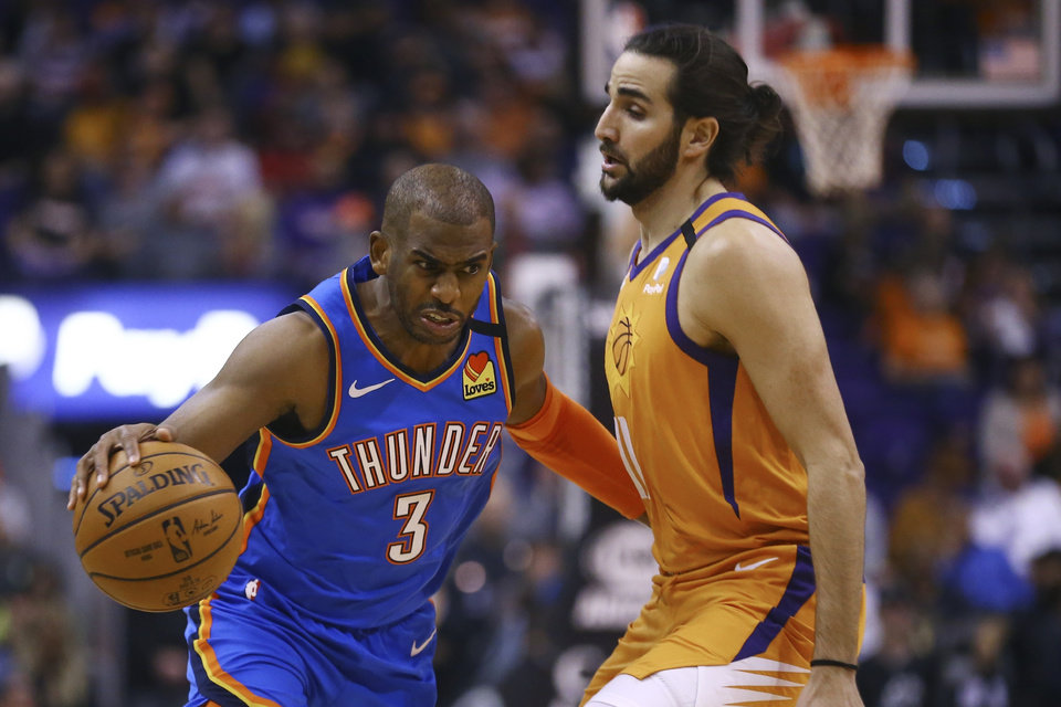Photo - Oklahoma City Thunder guard Chris Paul (3) dribbles past Phoenix Suns guard Ricky Rubio, right, during the first half of an NBA basketball game Friday, Jan. 31, 2020, in Phoenix. The Thunder defeated the Suns 111-107. (AP Photo/Ross D. Franklin)