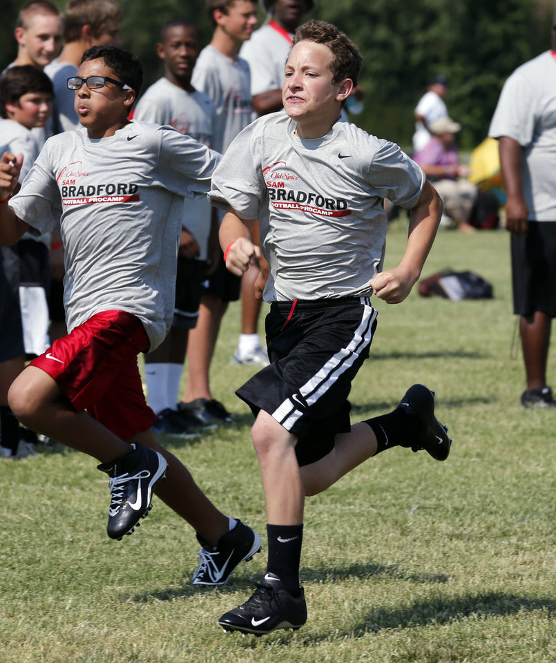 Photo - Camper Keaton Wingo, 14, (right) runs in a race at Sam Bradford's Football Camp on the campus of the University of Oklahoma on Wednesday, July 11, 2012, in Norman, Okla.  Photo by Steve Sisney, The Oklahoman