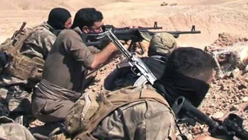 Photo - In this Tuesday, June 17, 2014 image taken from video obtained from British Broadcaster Sky, which has been authenticated based on its contents and other AP reporting, Kurdish soliders aim their weapons towards positions held by fighters of the Islamic State of Iraq and the Levant near Jalula, Iraq. Kurdish security forces are engaged in gun battles with Sunni militants in the northern Iraqi town of Jalula, according to British Broadcaster Sky. Footage showed Kurdish fighters known as peshmerga using heavy artillery and rockets to attack militant positions on Tuesday. (AP Photo/Sky via AP video)