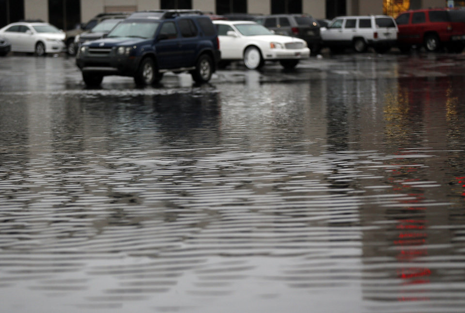 Photo - Water gathers in a parking lot of a shopping center on the southeast corner of NW 63rd and May during a thunder storm in Oklahoma City, Saturday, May 23, 2015. Photo by Nate Billings, The Oklahoman
