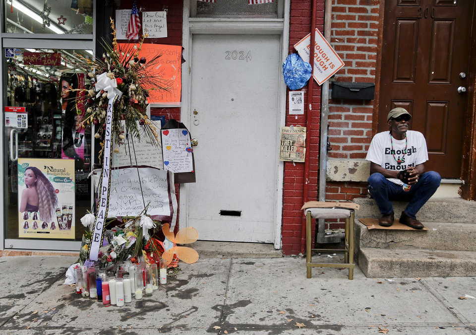 Photo - Doug Brinson sits on a stoop next to a makeshift memorial for Eric Garner, Friday, Aug. 1, 2014, in the Staten Island borough of New York. Garner died after he was put in a chokehold while being arrested at the site last month for selling untaxed loose cigarettes. On Friday, the medical examiner ruled Garner's death to be a homicide caused by a police chokehold. (AP Photo/Julie Jacobson)