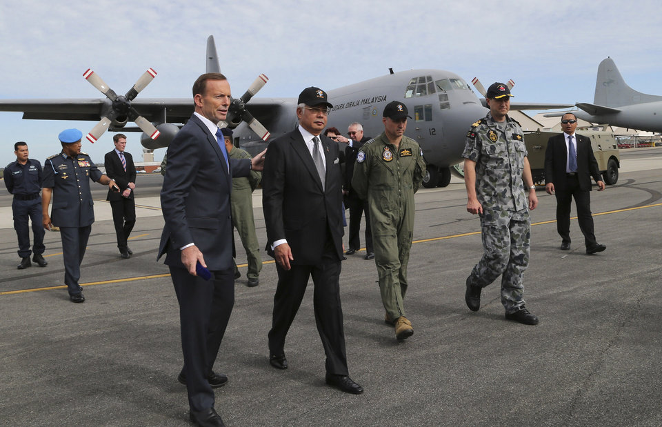 Photo - Australia's Prime Minister Tony Abbott, foreground left, and Malaysia Prime Minister Najib Razak, foreground second from left, accompanied by Australian Air Force Group Commander. Craig Heap, foreground second from right, and Commodore Peter Leavy commander of joint task force 658, walk on the tarmac at Royal Australian Air Force Base Pearce in Perth, Australia, Thursday, April 3, 2014. Razak is in Australia to to have talks with Abbott about the missing Malaysia Airline plane and to attend briefings with search crew members. (AP Photo/Rob Griffith, Pool)