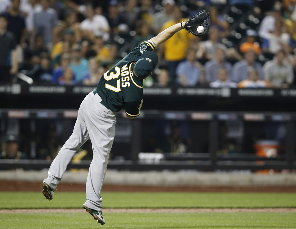 Photo - Oakland Athletics first baseman Brandon Moss (37) leaps to reach Travid d'Arnaud's eighth-inning pop out in an interleague baseball game against the New York Mets in New York, Wednesday, June 25, 2014. (AP Photo/Kathy Willens)
