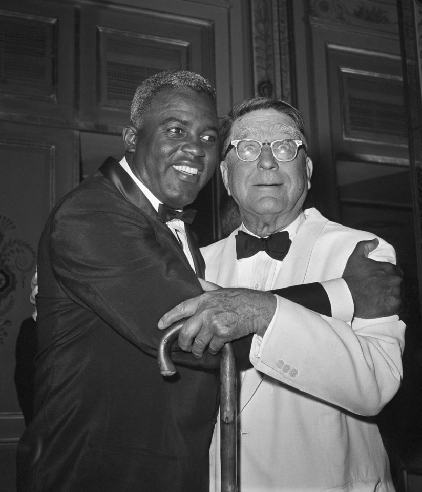"Photo - FILE - In this July 20, 1962 file photo, baseball player Jackie Robinson embraces Branch Rickey in New York. Rickey was general manager of the Brooklyn Dodgers when Robinson was hired. The home area of the late baseball executive Rickey expects increased interest in his southern Ohio roots from his depiction in the movie ""42,"" in which Harrison Ford plays the man who signed Jackie Robinson to challenge baseball's color line. (AP Photo/File)"