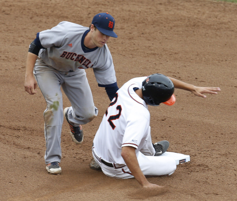 Photo - Bucknell's Greg Wasikowski tags Virginia's Daniel Pinero (22) out in the sixth inning at second base during an NCAA college baseball tournament regional game in Charlottesville, Va., Friday, May 30, 2014. Virginia won 10-1. (AP Photo/Steve Helber)