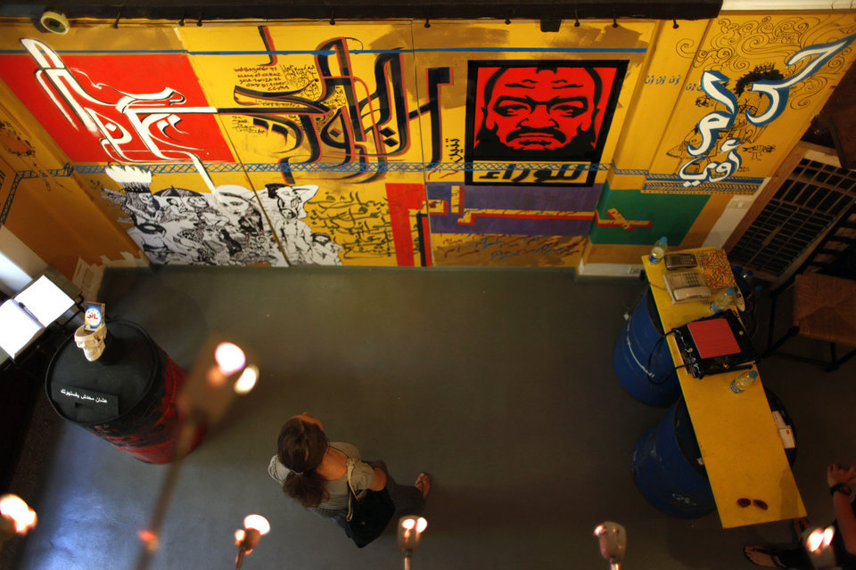 Photo -   In this Thursday, Oct. 4, 2012 photo, a woman inspects a mural with Arabic that reads