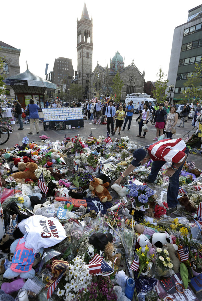 Photo - Volunteer Kevin Brown, of Boston, right, places a Teddy bear at a makeshift memorial near the Boston Marathon finish line in Boston's Copley Square Tuesday, May 7, 2013 in remembrance of the Boston Marathon bombings. (AP Photo/Steven Senne)