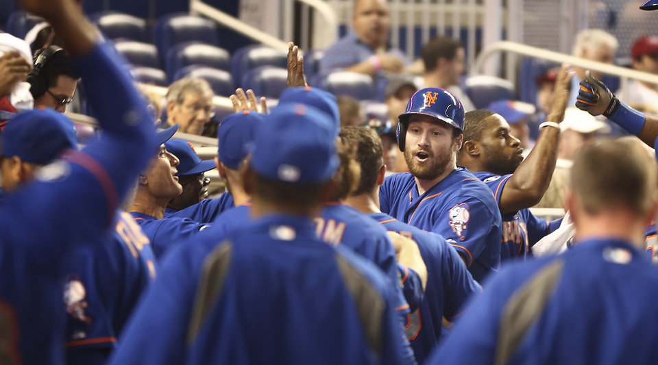 Photo - New York Mets batter Daniel Murphy (facing camera) celebrates in the dugout after hitting a three-run home run during the fourth inning of a baseball game in Miami against the Miami Marlins, Sunday, June 22, 2014. The Mets won 11-5. (AP Photo/J Pat Carter)