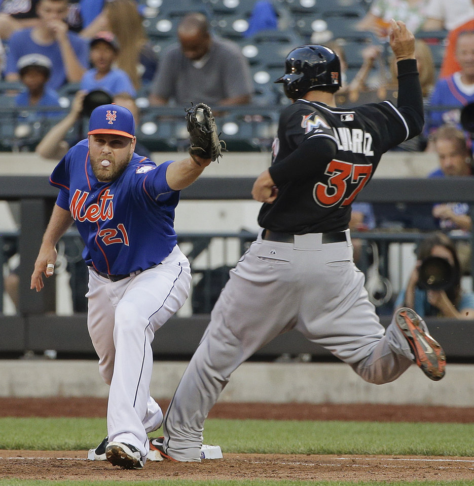 Photo - New York Mets first baseman Lucas Duda (21) takes the throw to the bag ahead of Miami Marlins' Henderson Alvarez (37) for an out in the third inning of a baseball game, Friday, July 11, 2014, in New York. (AP Photo/Julie Jacobson)