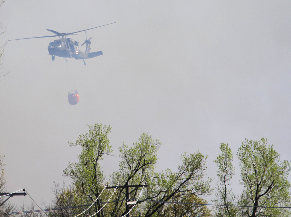 Photo - An Oklahoma National Guard helicopter drops water on a large grassfire near Spencer Jones Road and Westminster, Wednesday, April 6, 2011 in Oklahoma City, Okla. Photo by Sarah Phipps, The Oklahoman