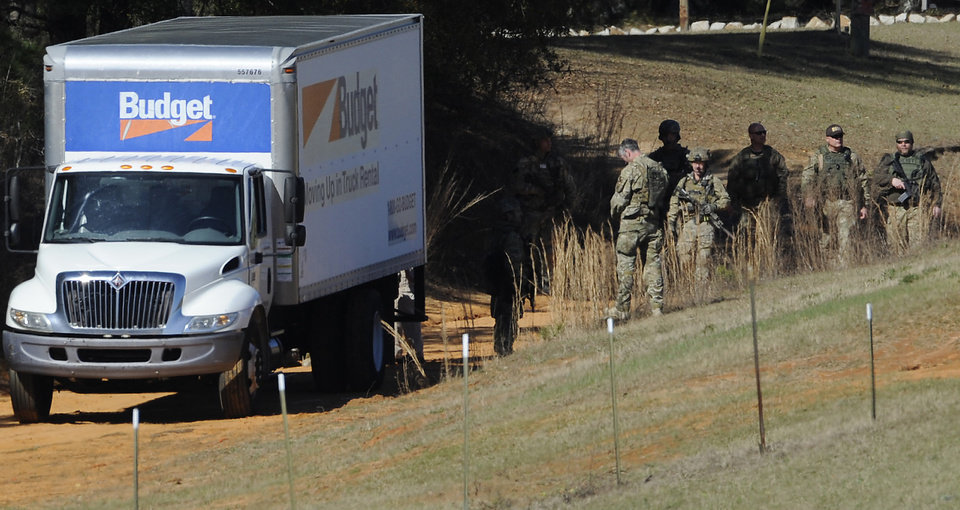 Photo - Authorities gather at the Dale County hostage scene in Midland City, Ala. on Thursday morning, Jan. 31, 2013. A gunman holed up in a bunker with a young hostage has kept law officers at bay since the standoff began when he killed a school bus driver and dragged the boy away, authorities said. (AP Photo/Montgomery Advertiser, Mickey Welsh)