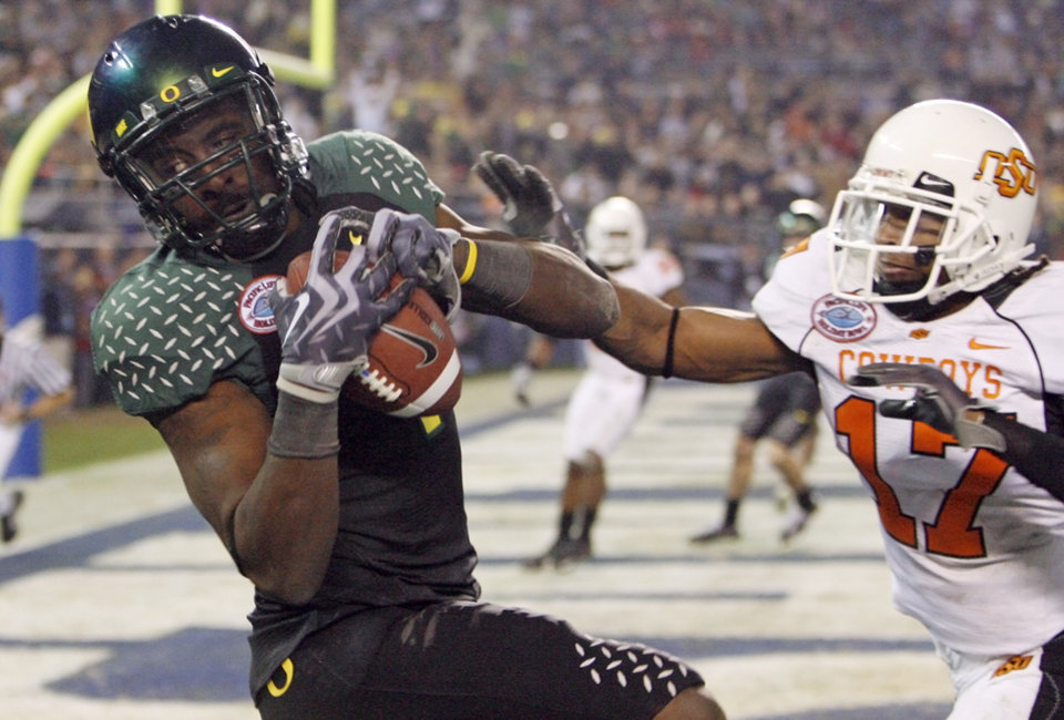 Photo - Oregon's Jaison Williams (4) catches a pass for a touchdown as OSU's Jacob Lacey (17) defends in the fourth quarter of the Holiday Bowl college football game between Oklahoma State and Oregon at Qualcomm Stadium in San Diego, Tuesday, Dec. 30, 2008. Oregon won, 42-31. PHOTO BY NATE BILLINGS, THE OKLAHOMAN