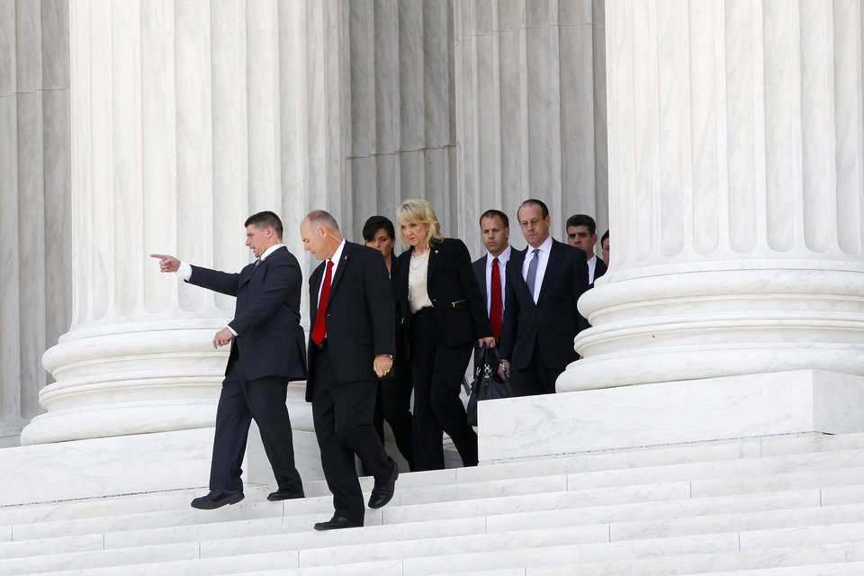 Arizona Gov. Jan Brewer, center, walks out after the Supreme Court in Washington, Wednesday, April 25, 2012, after the court\'s hearing on Arizona\'s