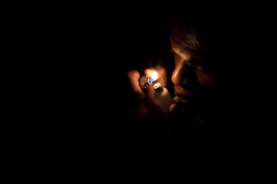 "In this photo taken Dec. 8, 2012, a man smokes crack at a slum in Rio de Janeiro, Brazil. The South American country began experiencing a public health emergency in recent years as demand for crack boomed and open-air ""cracolandias,"" or crack lands, popped up in the sprawling urban centers of Rio and Sao Paulo, with hundreds of users gathering to smoke the drug. The federal government announced in early 2012 that more than $2 billion would be spent to fight the epidemic, with the money spent to train local health care workers, purchase thousands of hospital and shelter beds for emergency treatment, and create transitional centers for recovering users. (AP Photo/Felipe Dana)"
