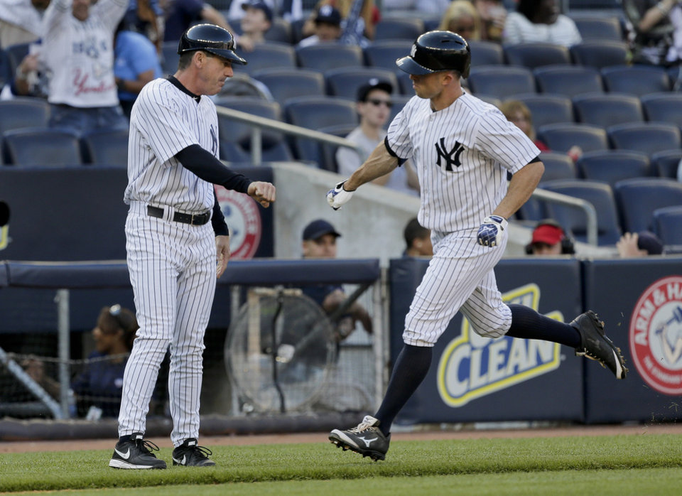 Photo - New York Yankees' Brett Gardner (11) is congratulated by third base coach Rob Thompson as he rounds the bases after hitting home run against the Pittsburgh Pirates during the sixth inning of a baseball game, Saturday, May 17, 2014, in New York. (AP Photo/Julie Jacobson)