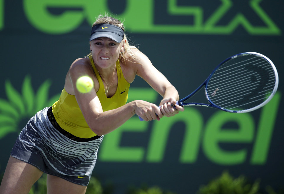 Photo - Maria Sharapova, of Russia, returns to Petra Kvitova, of Czech Republic, at the Sony Open Tennis tournament, Tuesday, March 25, 2014, in Key Biscayne, Fla. (AP Photo/Lynne Sladky)