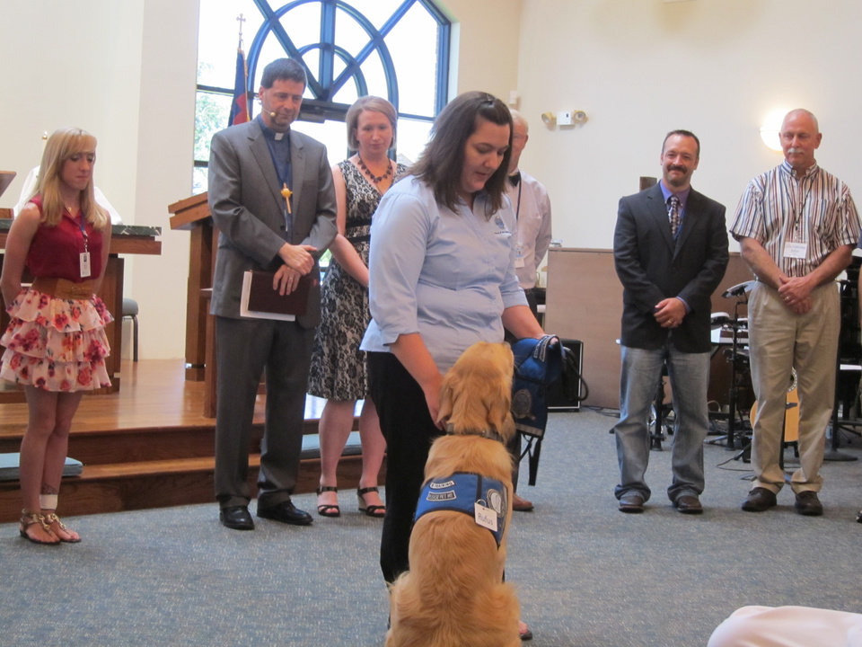 Photo -  Sherry Bolosan, with Lutheran Church Charities, prepares to formally pass Rufus Comfort Dog's leash to the Rev. Mark Erler and the congregation at St. Mark Lutheran Church in Edmond. Photo by Carla Hinton, The Oklahoman
