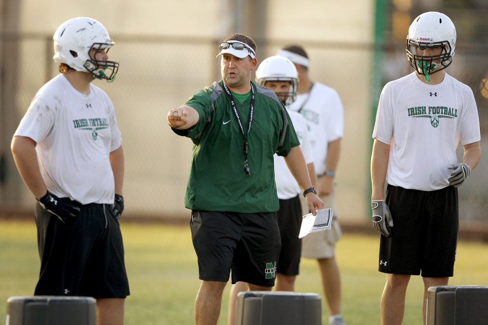 Photo - Bishop McGuinness coach Justin Jones works with his team during football practice in Oklahoma City, Wednesday, August 10, 2011. Photo by Bryan Terry, The Oklahoman