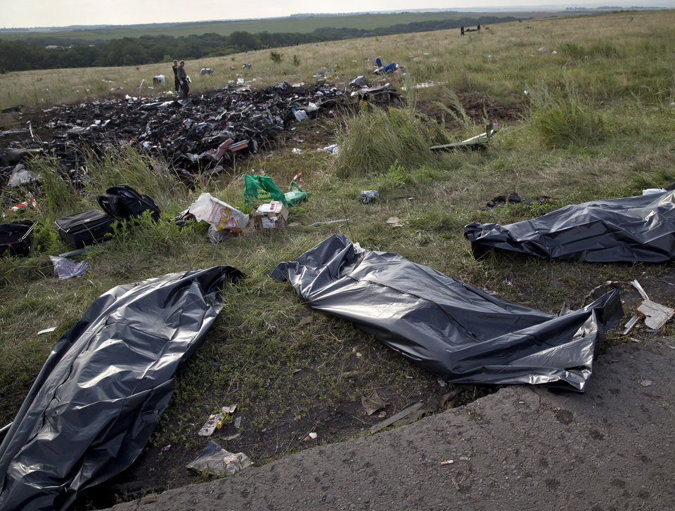 Photo - Bodies of victims are covered in plastic sacks at the crash site of Malaysia Airlines Flight 17 near the village of Hrabove, eastern Ukraine, Saturday, July 19, 2014. World leaders demanded Friday that pro-Russia rebels who control the eastern Ukraine crash site of Malaysia Airlines Flight 17 give immediate, unfettered access to independent investigators to determine who shot down the plane. (AP Photo/Vadim Ghirda)
