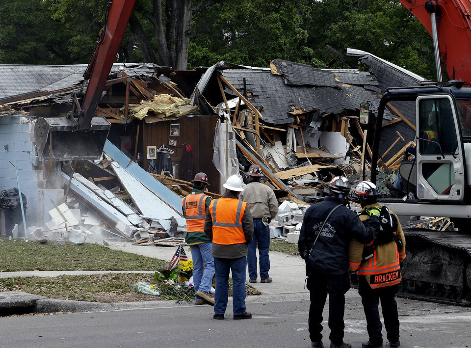 Photo - Demolition experts watch as the home of Jeff Bush, 37,  is destroyed Sunday, March 3, 2013, after a sinkhole opened up underneath it late Thursday evening swallowing Bush, 37, in Seffner, Fla. The 20-foot-wide opening of the sinkhole was almost covered by the house, and rescuers said there were no signs of life since the hole opened Thursday night. (AP Photo/Chris O'Meara)