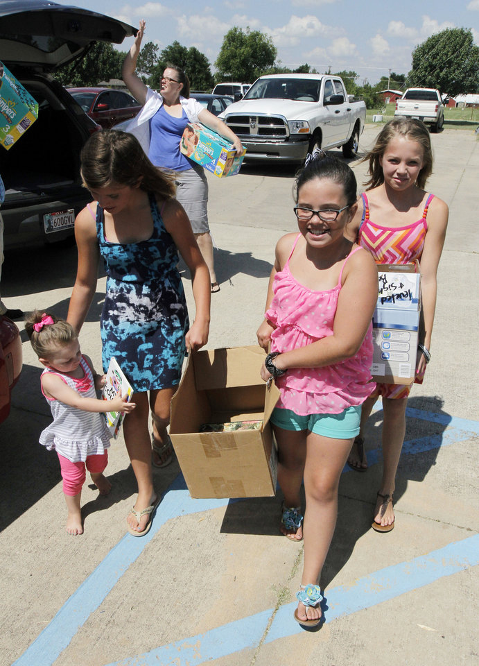 Photo - 2 year old Elliot McMillan, left, Daren McMillan, 11, Brynn McMillan, 10, and Makayla Ford, 12, bring books to the Eastlake Cumberland Presbyterian Church in Oklahoma City, OK, Monday, July 1, 2013, which they collected for tornado damaged schools by running a lemonade stand. Photo by Paul Hellstern, The Oklahoman