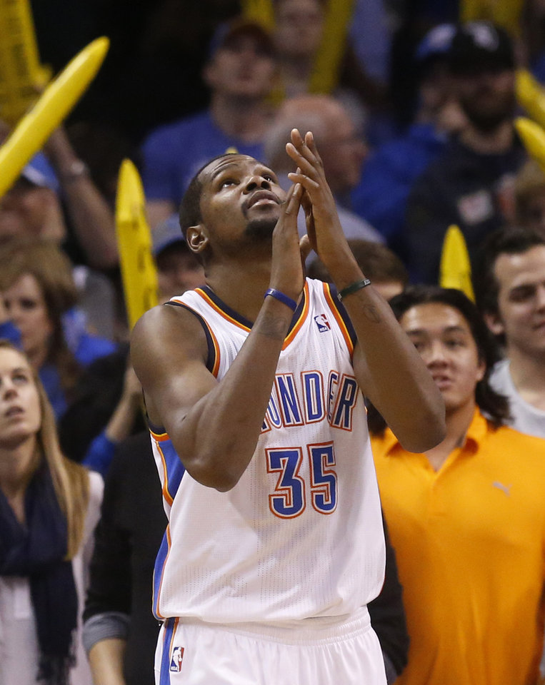 Photo - Oklahoma City Thunder forward Kevin Durant (35) claps his hands as he looks up at the scoreboard as the game clock winds down in the fourth quarter of an NBA basketball game against the Sacramento Kings in Oklahoma City, Sunday, Jan. 19, 2014. Oklahoma City won 108-93. (AP Photo/Sue Ogrocki)