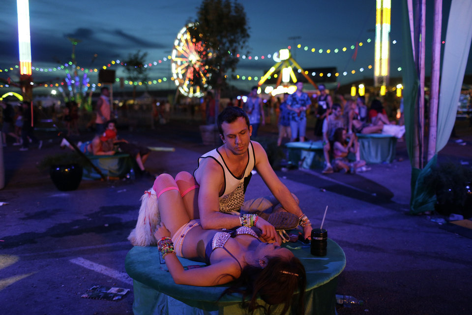 Photo - John Cameron and Julia French take a break during the Electric Daisy Carnival, Saturday, June 21, 2014, in Las Vegas. Ample spaces between stages allow festival goers to escape the loud music and pulsating masses of people. (AP Photo/John Locher)