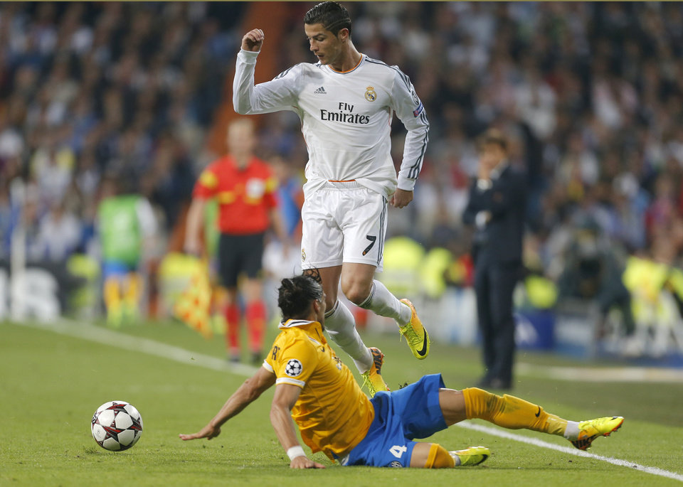 Photo - Real's Cristiano Ronaldo, top, and Juventus' Martin Caceres, bottom,  challenge for the ball during a Group B Champions League soccer match between Real Madrid and Juventus at the Santiago Bernabeu stadium in   Madrid, Spain, Wednesday Oct. 23, 2013. (AP Photo/Paul White)