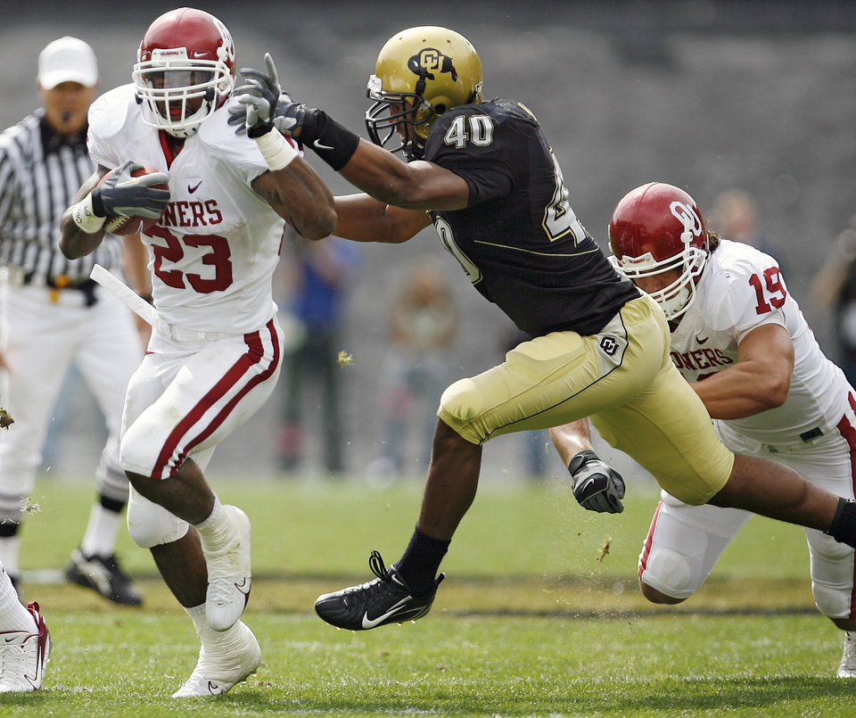 Photo - Oklahoma's Allen Patrick (23) gets past Colorado's Brad Jones (40) on his way to a touchdown during the first half of the college football game between the University of Oklahoma Sooners (OU) and the University of Colorado Buffaloes (CU) at Folsom Field on Saturday, Sept. 28, 2007, in Boulder, Co.  By Bryan Terry, The Oklahoman