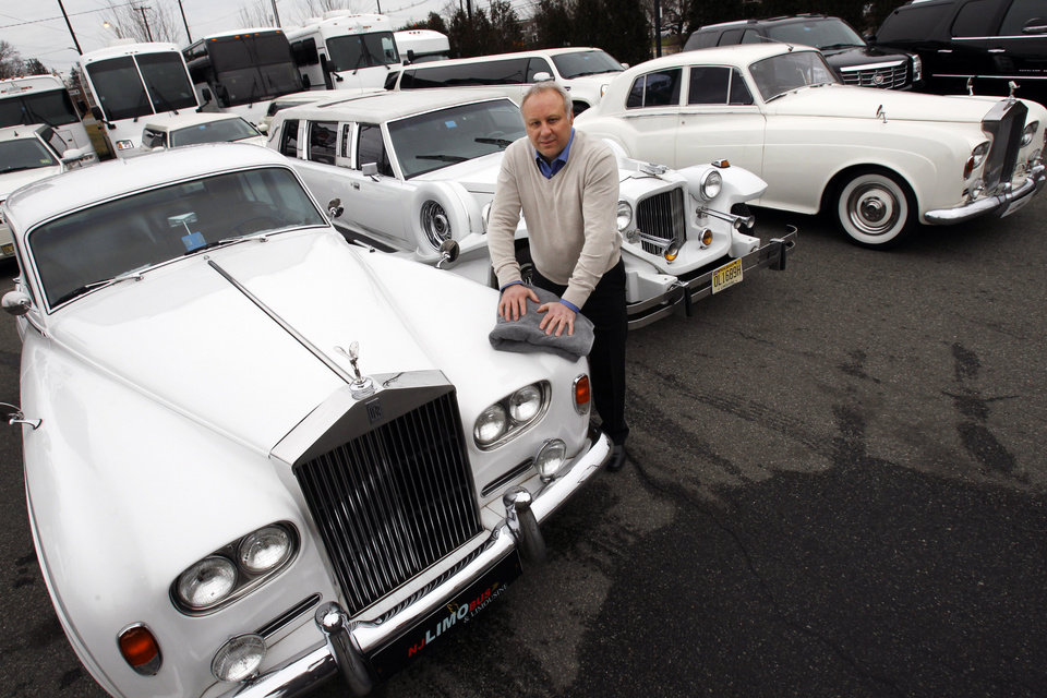 In this Tuesday, Jan. 15, 2013, photo, Joe Brasco, of  New Jersey Limo Bus & Limousine,wipes off a Rolls Royce in Fairfield, N.J. The flu season has created a scramble for New Jersey Limo Bus & Limousine as two of the company's seven full-time employees called in sick at the same time, but the Brascos have managed to find substitutes when workers have called in sick. (AP Photo/Mel Evans)