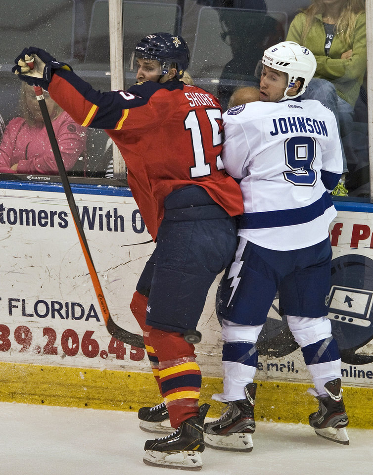 Photo - Florida Panthers' Drew Shore (15) and Tampa Bay Lightning's Tyler Johnson (9) look for the puck during the first period of an NHL preseason hockey game Thursday, Sept. 26, 2013, in Estero, Fla. (AP Photo/Steve Nesius)