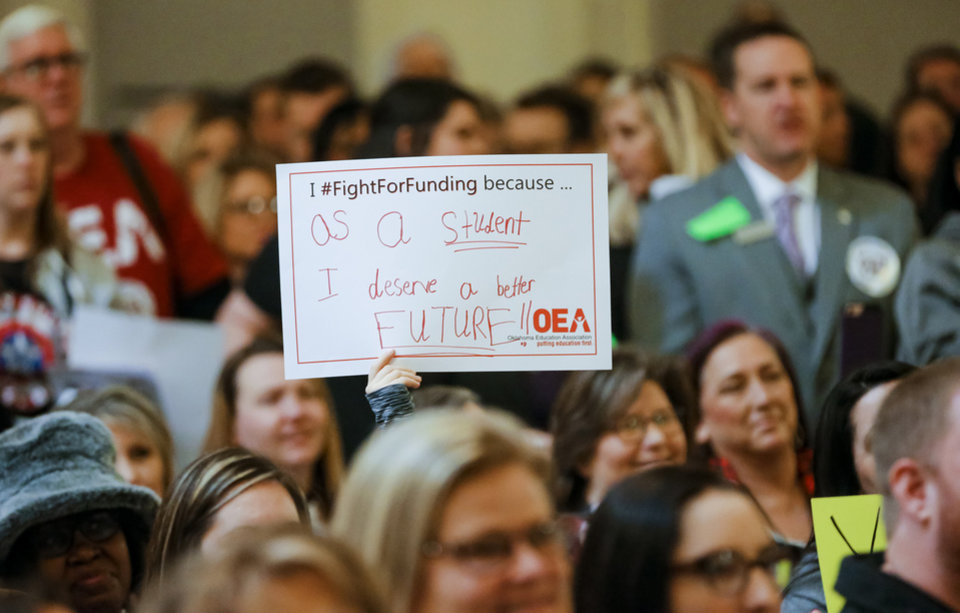 Photo - A student holds up a sign during a rally to support the Step Up Oklahoma Plan at the state capitol in Oklahoma City, Okla. on Monday, Feb. 12, 2018.    Photo by Chris Landsberger, The Oklahoman