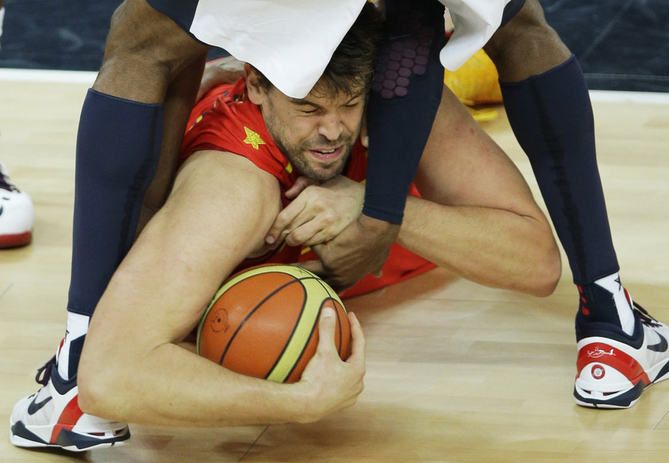 Spain's Marc Gasol dives at the feet of United States' Kobe Bryant for the basketball during the men's gold medal basketball game at the 2012 Summer Olympics, Sunday, Aug. 12, 2012, in London. (AP Photo/Matt Slocum)