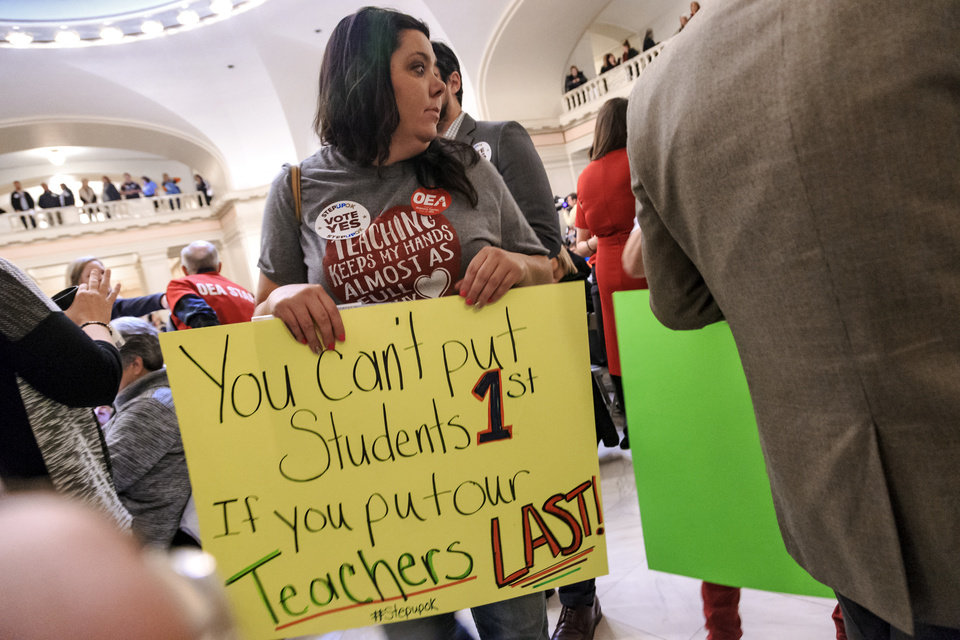 Photo - Locus Grove teacher Julie Atchley carries her sign as she make her way to the rally to support the Step Up Oklahoma Plan at the state capitol in Oklahoma City, Okla. on Monday, Feb. 12, 2018.    Photo by Chris Landsberger, The Oklahoman