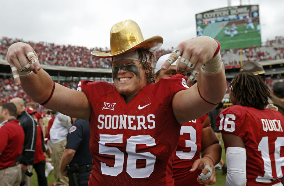 Photo - Oklahoma's Ty Darlington (56) celebrates while wearing the Golden Hat Trophy after the Red River Showdown college football game between the University of Oklahoma Sooners (OU) and the University of Texas Longhorns (UT) at the Cotton Bowl in Dallas on Saturday, Oct. 11, 2014. 