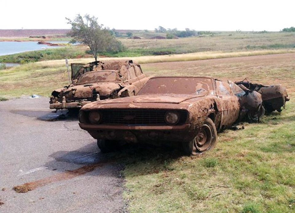 This Sept. 17, 2013, photo shows two cars recovered from Foss Lake, Okla. The Oklahoma State Medical ExaminerÂ's Office says authorities have recovered skeletal remains of multiple bodies in the Oklahoma lake where the two decades-old cars were pulled from the water by a dive team. (AP Photo/Daily Elk Citian, Laura Eastes) ORG XMIT: TXKJ101