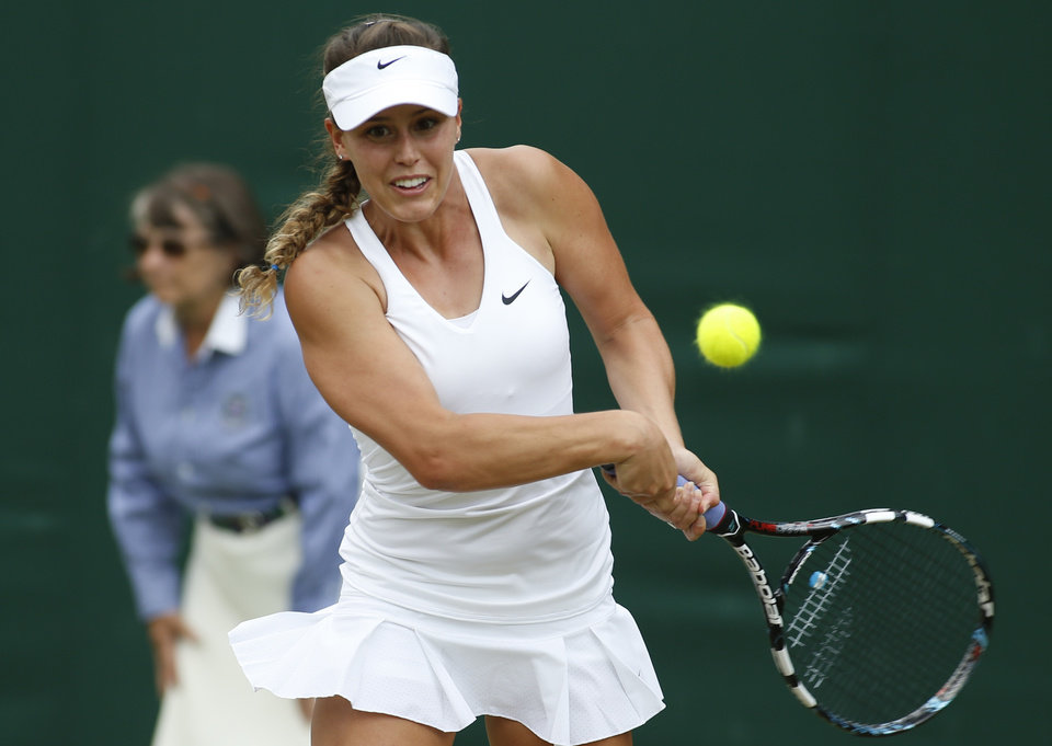 Photo - Michelle Larcher De Brito of Portugal plays a return to Svetlana Kuznetsova of Russia during their first round match at the All England Lawn Tennis Championships in Wimbledon, London, Tuesday, June 24, 2014. (AP Photo/Alastair Grant)