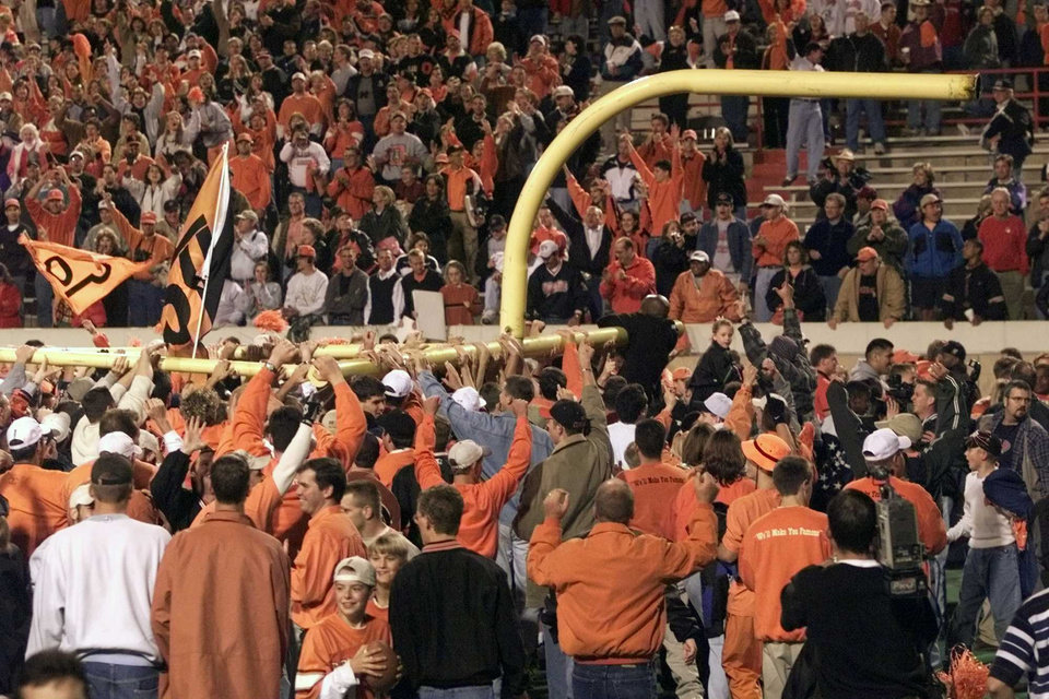 Photo - OSU fans carry a goal post off the field after the Cowboys beat OU, 41-26, during the Bedlam college football game in Stillwater, Okla. Oct. 24, 1998. Photo by Doug Hoke, The Oklahoman