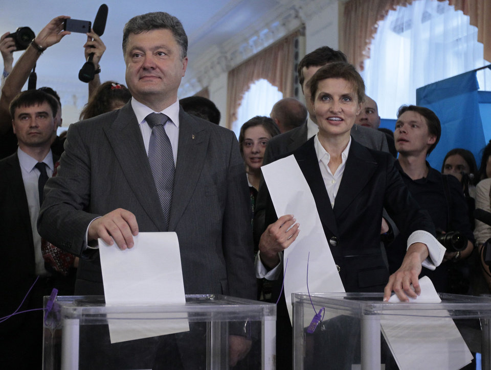 Photo - Ukrainian presidential candidate Petro Poroshenko, left,  and his wife Maria, right, cast their ballots at a polling station during the presidential election in Kiev, Ukraine, Sunday, May 25, 2014. Ukraine's critical presidential election got underway Sunday under the wary scrutiny of a world eager for stability in a country rocked by a deadly uprising in the east. (AP Photo/Sergei Chuzavkov)