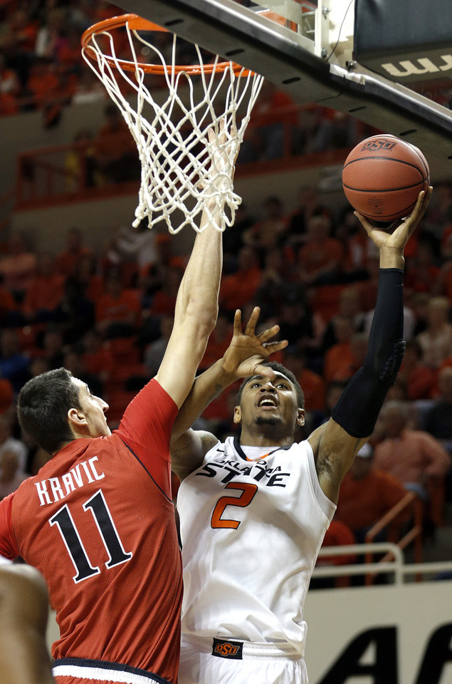Photo - Oklahoma State's Le'Bryan Nash (2) shoots over Dejan Kravic (11) during the men's college basketball game between Oklahoma State and Texas Tech at Gallagher-Iba Arena in Stillwater, Okla., Saturday, Feb. 22, 2014. OSU won 84-62. 